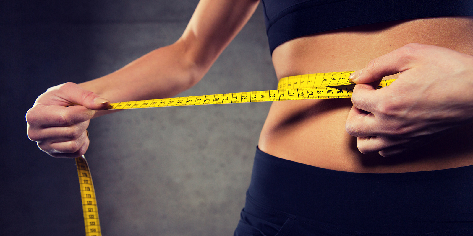 close up of woman measuring waist size by tape in gym